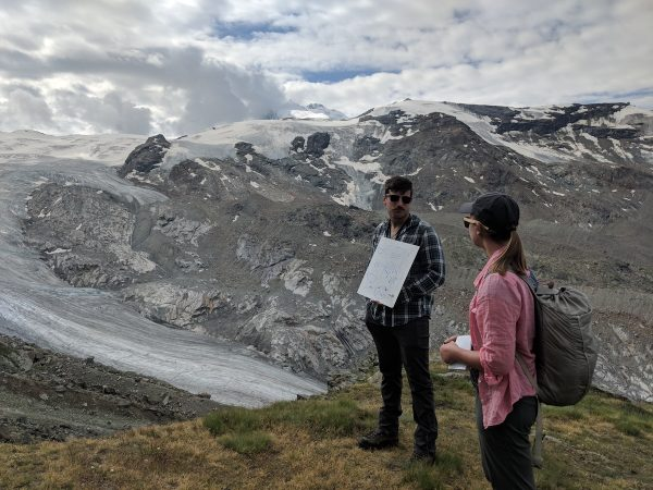 Two people standing in front of a glacier in the mountains.