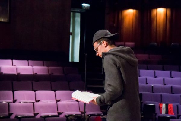 A student rehearsing lines on stage.