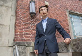 Zhengyuan Zhu in front of brick building