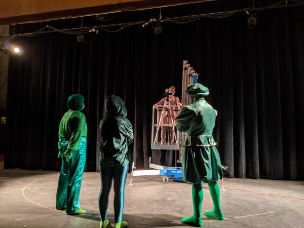 Three actors dressed in green on stage