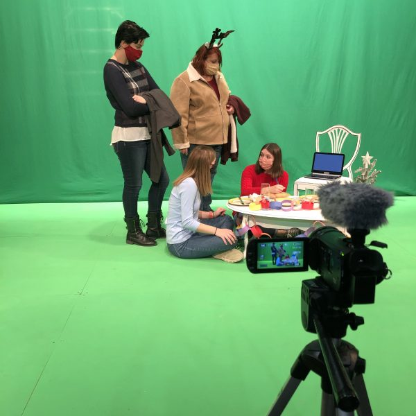 Four actors have a conversation in front of a green screen