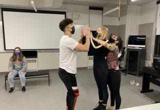 Four actors rehearse in a classroom
