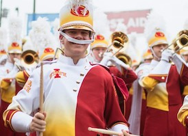 Student in band uniform, with drumsticks