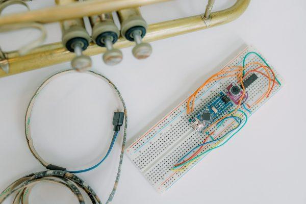 The Varsity Instrument Lights prototype next to a trumpet.