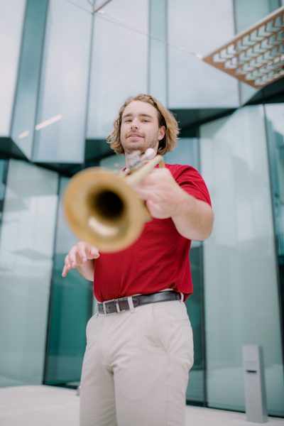 Jacob Schmieder holding a trumpet.
