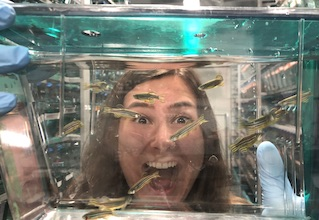 Student smiling behind zebrafish tank.