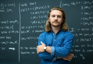 Student posed with chalkboard of math equations