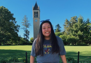 Student posed in front of campanile