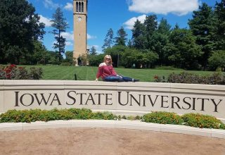 Student sitting in front of campanile