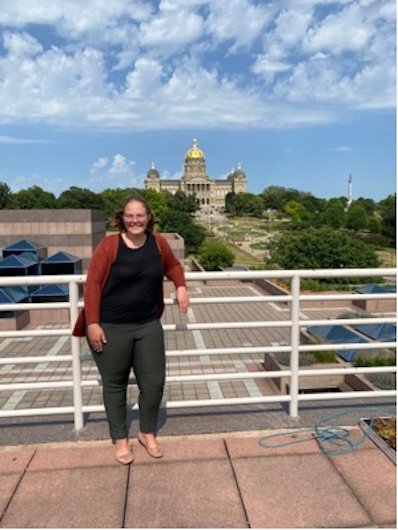 Person leaning against railing, Iowa Capitol dome in the background